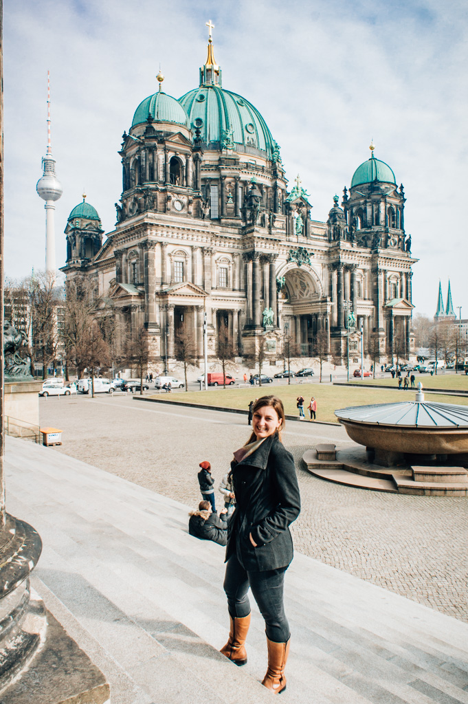 Woman with black jacket standing on the Museuminsel in Berlin with domed church in background
